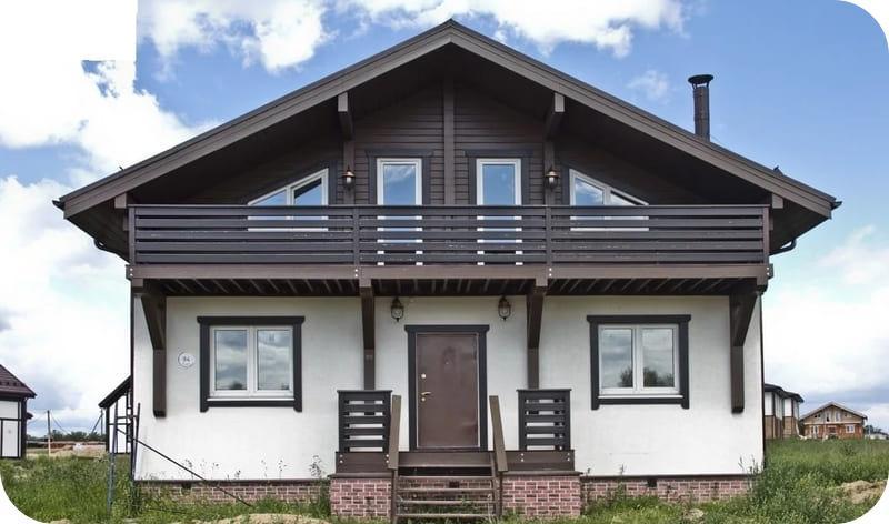 Снизу газобетонный дом с мансардой отделан штукатуркой, а сверху композитной древесиной
