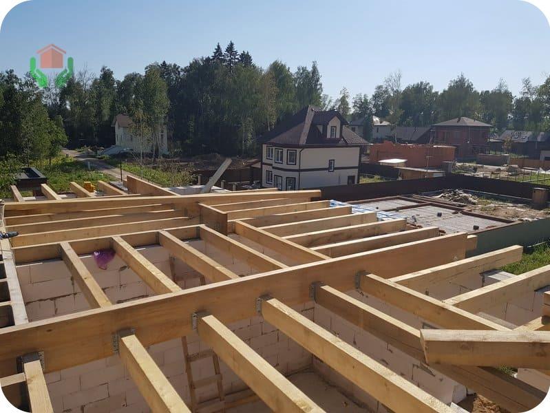 Чердачное деревянное перекрытие в газобетонном доме: концы балок выступают за контур стены и формируют свес крыши